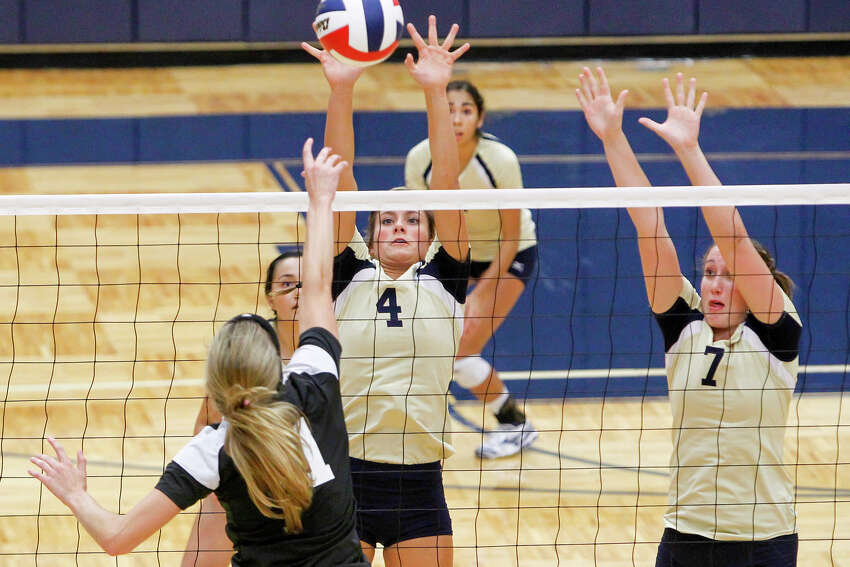 O'Connor's McKenzie Kelley (center) blocks a shot by Clarks's Katie Mattson as Laura Fox (right) tries to help out during their District 27-5A volleyball match at Paul Taylor Field House on Tuesday, Aug. 27, 2013. O