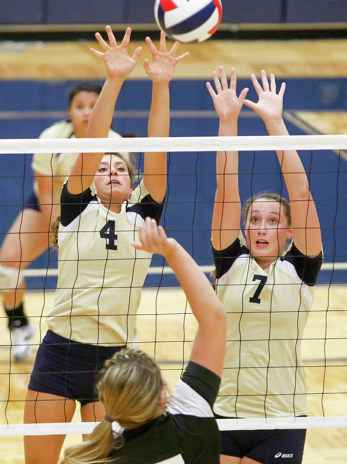 O'Connor's McKenzie Kelley (left) and Laura Fox leap to try to block a shot by Clark's Megan Pattison during their District 27-5A volleyball match at Paul Taylor Field House on Tuesday, Aug. 27, 2013. O