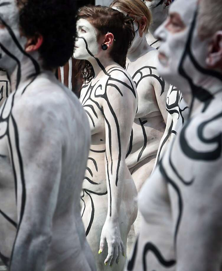 Wearing only white wash and black pigment, models painted by artist Andy Golub gather in New York's Times Square. Golub made the 