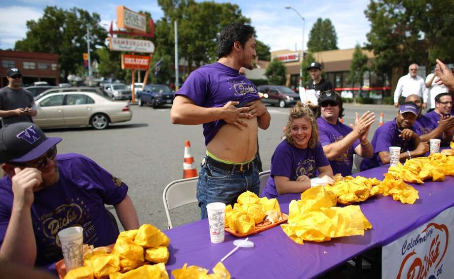Frank Painter shows off his belly after winning a cheeseburger eating contest at Dick's Drive-In on 45th Street in Wallingford. The contest pitted legendary Husky football players and fans of the restaurant against each other as they devoured cheeseburgers. Photo: JOSHUA TRUJILLO, SEATTLEPI.COM