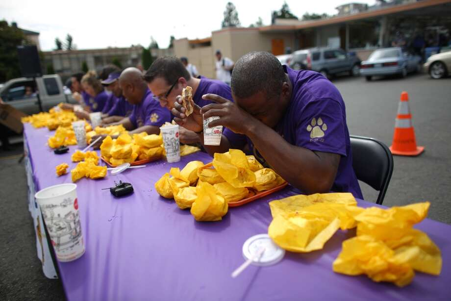 Former Husky player and NFL player Lawyer Milloy takes a break during a cheeseburger eating contest at Dick's Drive-In on 45th Street in Wallingford. The contest pitted legendary Husky football players and fans of the restaurant against each other as they devoured cheeseburgers. Photo: JOSHUA TRUJILLO, SEATTLEPI.COM