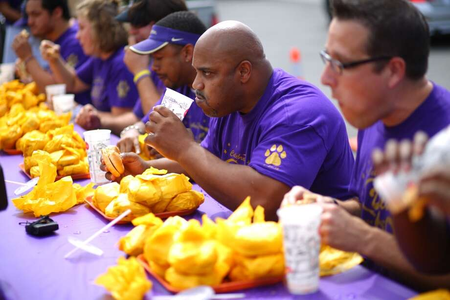 Former Husky player Greg Lewis chows down during a cheeseburger eating contest at Dick's Drive-In on 45th Street in Wallingford. The contest pitted legendary Husky football players and fans of the restaurant against each other as they devoured cheeseburgers. Photo: JOSHUA TRUJILLO, SEATTLEPI.COM