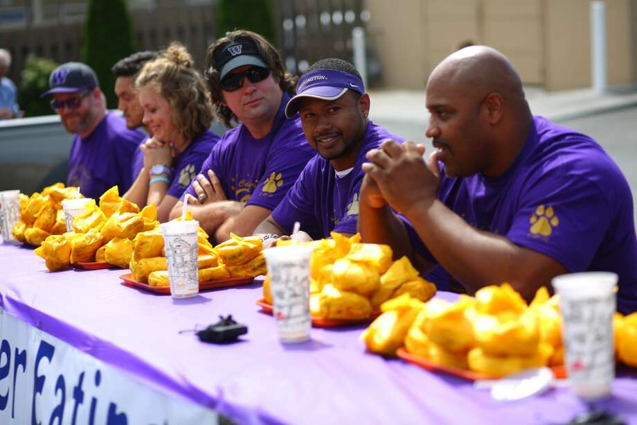 Contestants, from left, Jake Bowman, Frank Painter, Jacqueline Blackmore, Jason Chorak, Mario Bailey and Greg Lewis wait for the start during a cheeseburger eating contest at Dick's Drive-In on 45th Street in Wallingford. The contest pitted legendary Husky football players and fans of the restaurant against each other as they devoured cheeseburgers. Photo: JOSHUA TRUJILLO, SEATTLEPI.COM