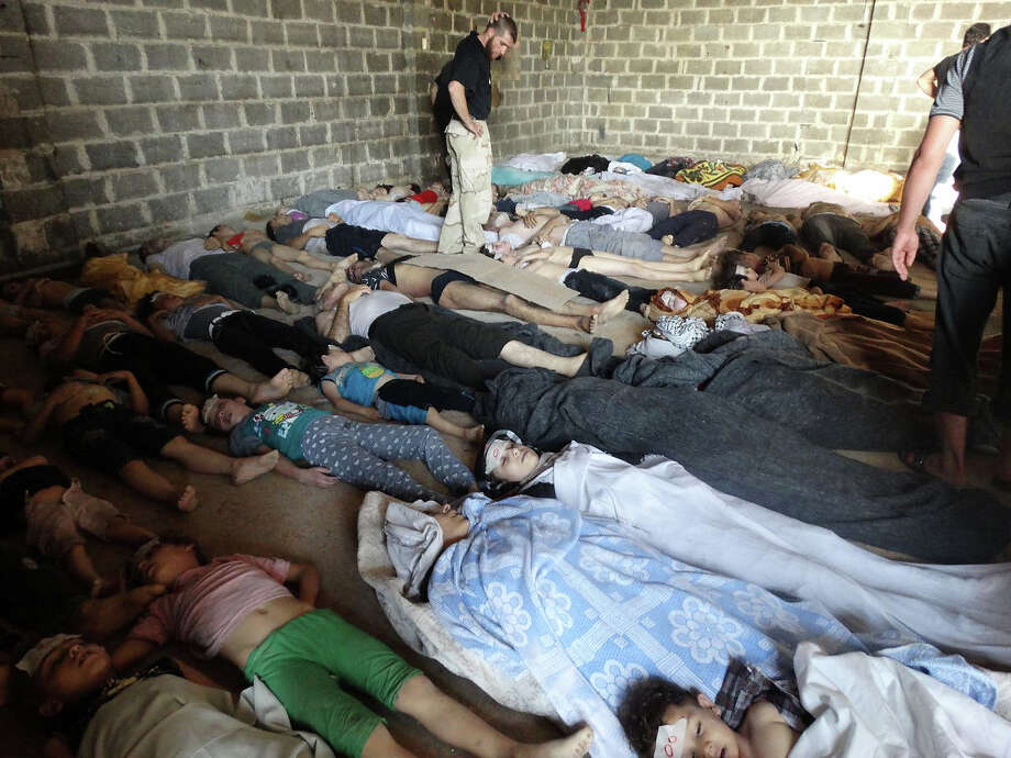 """This image provided by Shaam News Network on Thursday, Aug. 22, 2013,  which has been authenticated based on its contents and other AP reporting, purports to show dead bodies after an attack on Ghouta, Syria on Wednesday, Aug. 21, 2013. Syrian government forces pressed their offensive in eastern Damascus on Thursday, bombing rebel-held suburbs where the opposition said the regime had killed more than 100 people the day before in a chemical weapons attack. The government has denied allegations it used chemical weapons in artillery barrages on the area known as eastern Ghouta on Wednesday as """"absolutely baseless."""" Photo: Uncredited, ASSOCIATED PRESS / AP2013"""