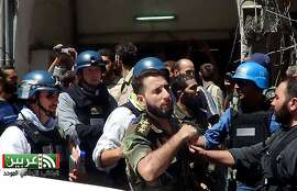 In this citizen journalism image provided by the United media office of Arbeen which has been authenticated based on its contents and other AP reporting, UN investigation team with blue helmets, walk with Syrian rebels in Damascus countryside of Zamalka, Syria, Wednesday, Aug. 28, 2013. U.N. chemical weapons experts headed to a Damascus suburb on Wednesday for a new tour of areas struck by a purported poison gas attack, activists said, as Western powers laid the groundwork for a possible punitive strike and the U.N. chief pleaded for more time for diplomacy. (AP Photo/United media office of Arbeen)