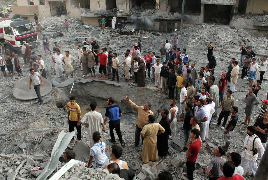"People gather around a crater at the scene of an explosion in the northern Syrian city of Raqqa, early on August 7, 2013. UN weapons inspectors tasked with looking into claims of chemical weapons use in Syria are ""completing their preparations"" in The Hague before heading to Damascus, the United Nations said. Photo: AFP, AFP/Getty Images / 2013 AFP"