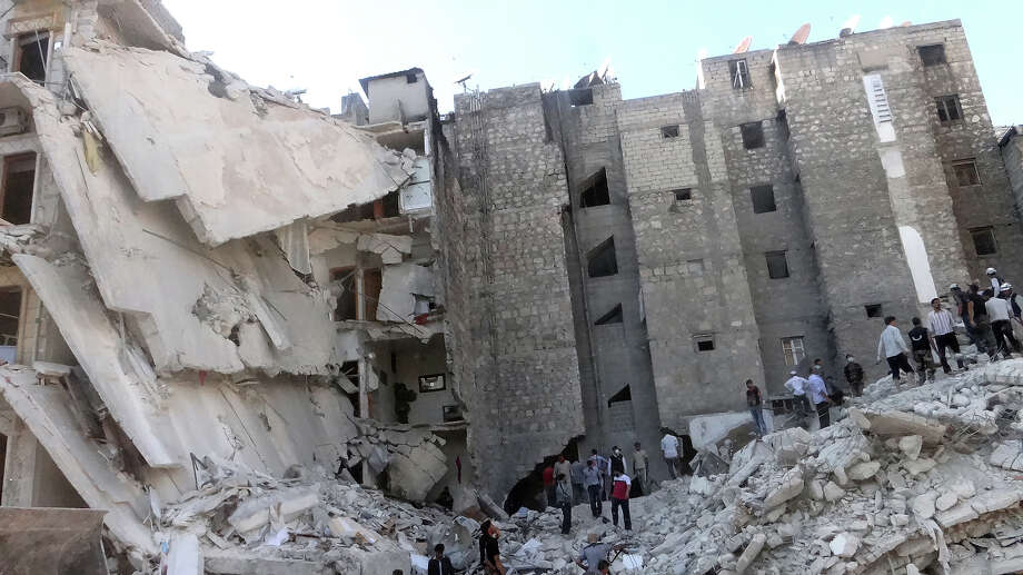 People search the rubble of a building which collapsed after it was allegedly bombed from the air during clashes between rebel fighter and pro-government troops on August 16, 2013, in the northern Syrian city of Aleppo. Syria's government said it has nothing to hide from a UN team of chemical weapons inspectors that it expects to visit the war-ravaged country in the coming days. Photo: AFP, AFP/Getty Images / 2013 AFP
