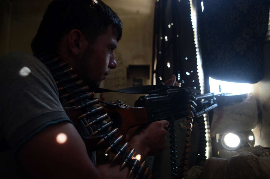 A rebel fighter takes aim at regime forces in the northern city of Aleppo on August 26, 2013. Syria's opposition accused pro-regime forces of opening fire at UN weapons inspectors on their way to a suspected chemical weapons site outside Damascus in a bid to hinder their investigation. Photo: AFP, AFP/Getty Images / 2013 AFP
