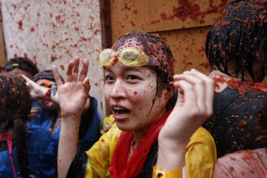 "A tourist reacts during the annual ""tomatina"" tomato fight fiesta in the village of Bunol. Photo: Alberto Saiz, Associated Press"
