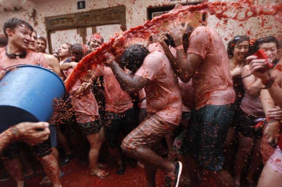 "People throw tomatoes at each other during the annual ""tomatina"" tomato fight fiesta in the village of Bunol, 50 kilometers outside Valencia, Spain, Wednesday, Aug. 28, 2013. Thousands of people are splattering each other with tons of tomatoes in the annual ""Tomatina"" battle in recession-hit Spain, with the debt-burdened town charging participants entry fees this year for the first time. Bunol town says some 20,000 people are taking part in Wednesday's hour-long street bash, inspired by a food fight among kids back in 1945. Participants were this year charged some 10 euros ($13) to foot the cost of the festival. Residents do not pay. Photo: Alberto Saiz, Associated Press"