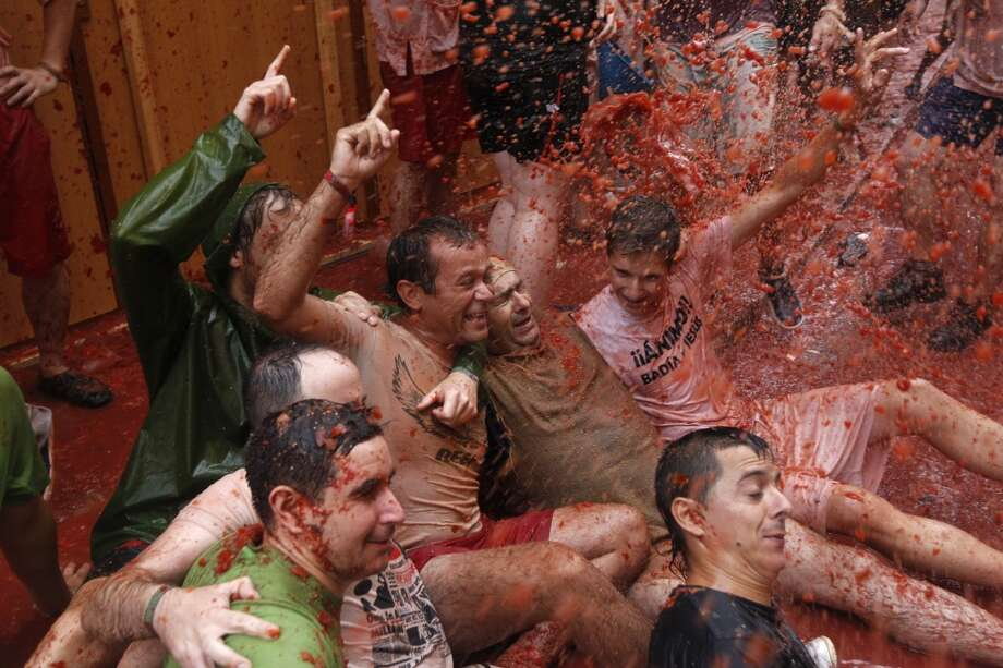 "People throw tomatoes at each other during the annual ""tomatina"" tomato fight fiesta in the village of Bunol. Photo: Alberto Saiz, Associated Press"