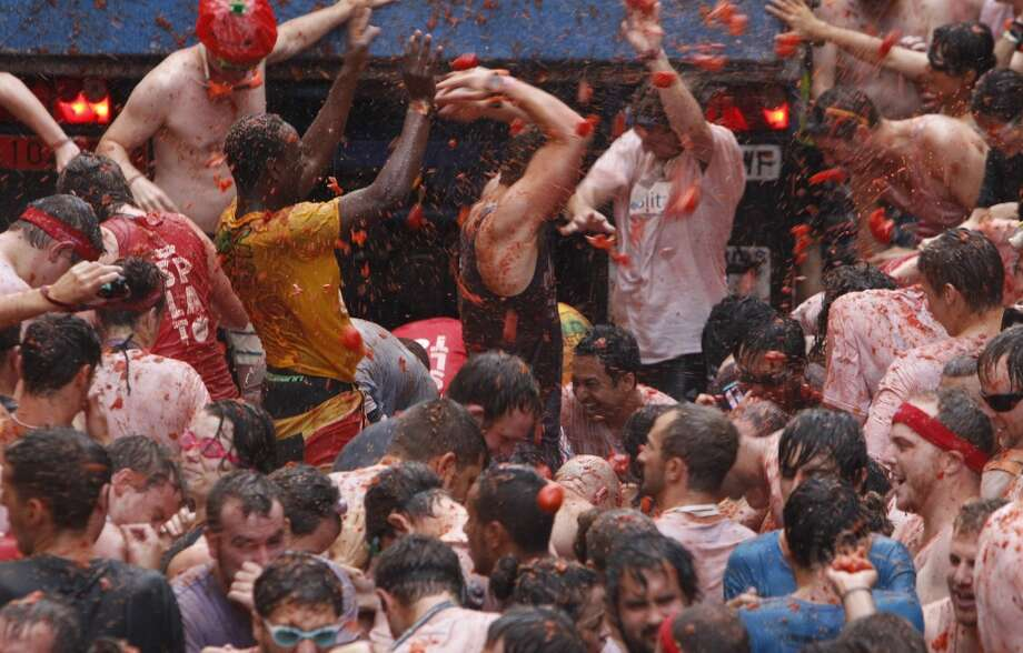 """Crowds of people throw tomatoes at each other during the annual """"tomatina"""" tomato fight fiesta in the village of Bunol. Photo: Alberto Saiz, Associated Press"""