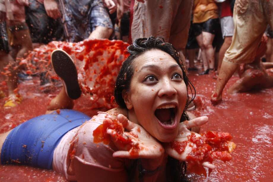"""A woman lays on a puddle of tomato juice during the annual """"tomatina"""" tomato fight fiesta in the village of Bunol. Photo: Alberto Saiz, Associated Press"""