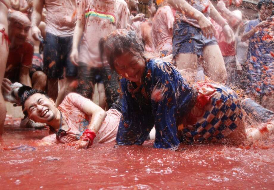 "People lay on a puddle of tomato juice during the annual ""tomatina"" tomato fight fiesta in the village of Bunol. Photo: Alberto Saiz, Associated Press"