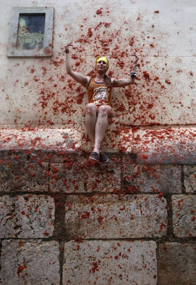 "A woman sits on a wall covered by tomato pulp during the annual ""tomatina"" tomato fight fiesta in the village of Bunol. Photo: Alberto Saiz, Associated Press"