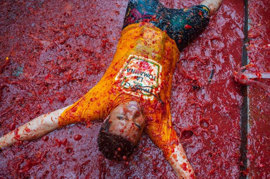A reveller baths in tomato pulp while participating the annual Tomatina festival . Photo: David Ramos, Getty Images