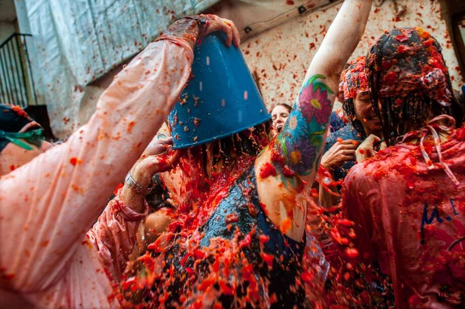 Revellers celebrate covered by tomato pulp while participating the annual Tomatina festival . Photo: David Ramos, Getty Images