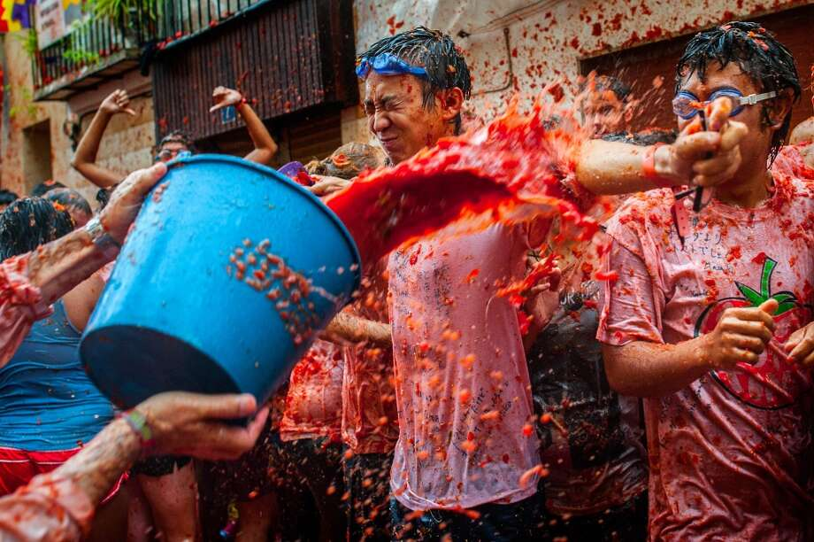 Revellers celebrate covered by tomato pulp while participating the annual Tomatina festival. Photo: David Ramos, Getty Images