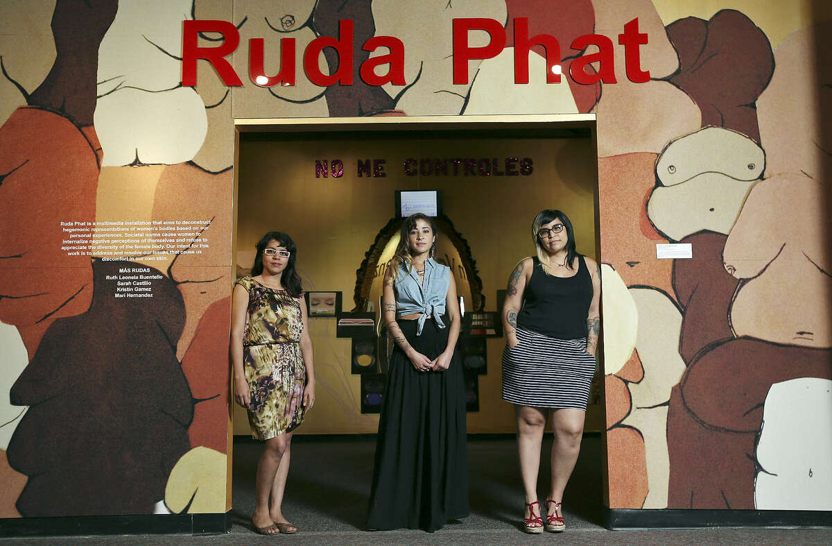 """Chicana arts collective Mas Rudas members Sarah Castillo (from left), Kristin Gamez and Mari Hernandez stand at the entrance to their exhibit """"Ruda Phat"""" at the Institute of Texan Cultures. Not pictured is Ruth Leonela Buentello."""