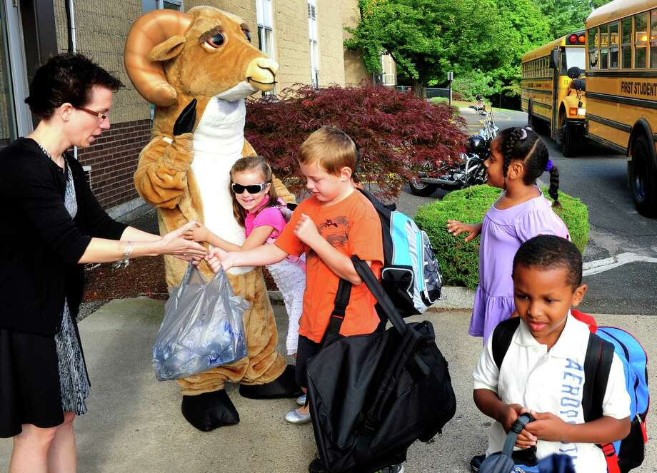 As new principal Trisha Soucy greets students, Madalyn Macko hugs Rocky the Ram at Rockwell School, on opening day in Bethel, Conn. Wednesday, Aug. 28, 2013. Photo: Michael Duffy / The News-Times