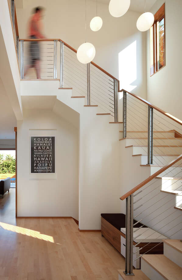 """To better establish (the entry) as a focal point, custom stainless steel posts with a cable rail and custom stair treads were added to the design of the entry stairway. A custom chandelier made of suspended globes of varying sizes hangs from the space's vaulted ceiling."" Photo: Lara Swimmer / (c) Lara Swimmer ALL RIGHTS RESERVED"