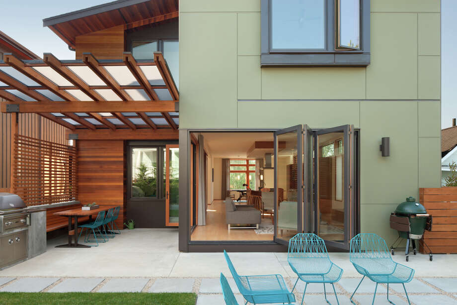 """""""The original design called for two large, punched sliding doors. These  were replaced with two bi-folding doors that open from the corner,  allowing for fluid access from the interior living area to the outdoor  concrete fire pit and built-in grill."""" Photo: Lara Swimmer / (c) Lara Swimmer ALL RIGHTS RESERVED"""