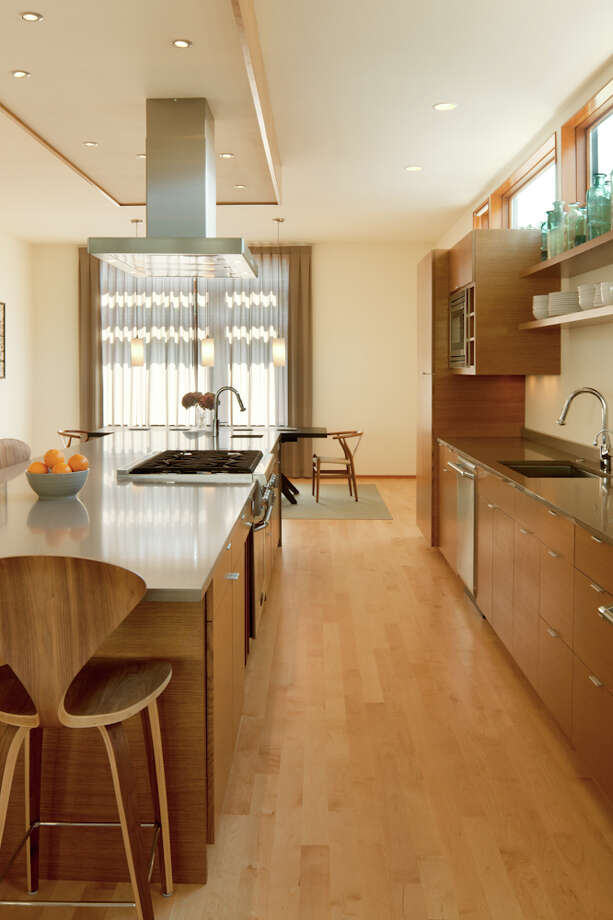The kitchen places island cabinets to allow for easy access, with a large cantilever at the corner of the silestone countertop and, above the island, a night sky soffit with rift-sawn oak that matches the cabinets. Photo: Lara Swimmer / (c) Lara Swimmer ALL RIGHTS RESERVED