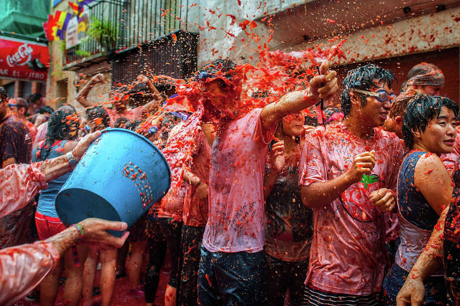 Revelers celebrate covered by tomato pulp while participating the annual Tomatina festival on August 28, 2013 in Bunol, Spain. An estimated 20,000 people threw 130 tons of ripe tomatoes in the world's biggest tomato fight held annually in this Spanish Mediterranean town. Photo: David Ramos, Getty Images / 2013 Getty Images