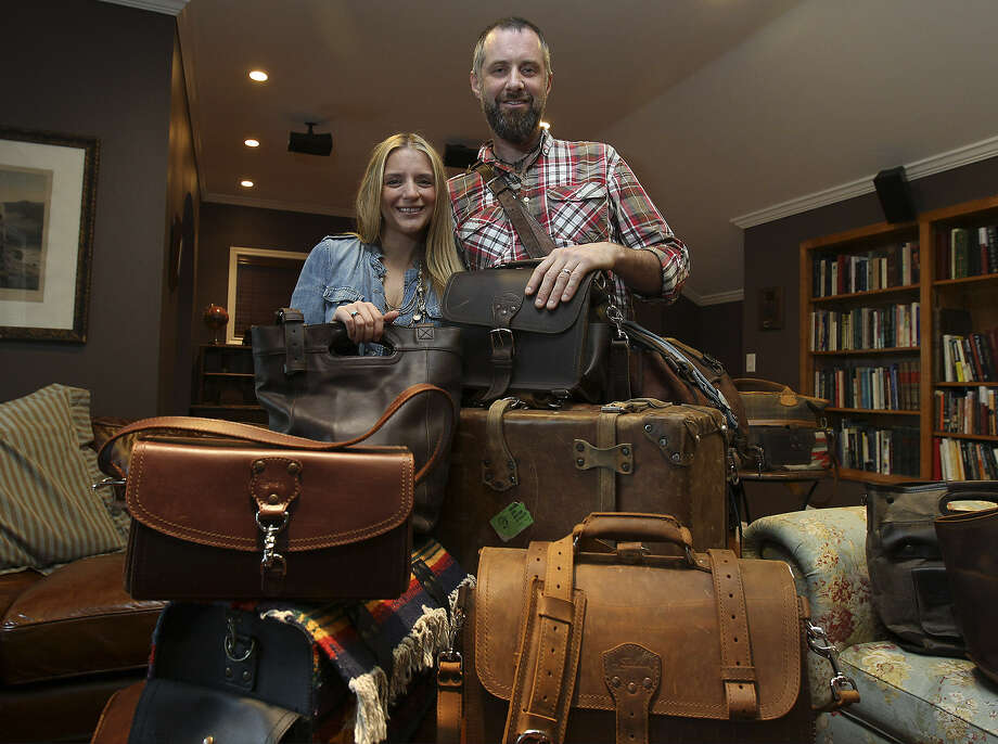 Dave Munson, president and owner of Saddleback Leather Co., and  wife, Suzette, pause with their merchandise. Saddleback began with sales of leather goods from Dave's vehicle.  Suzette also sells bags and jewelry on her retail website, www.Love41.com. Photo: Kin Man Hui / San Antonio Express-News
