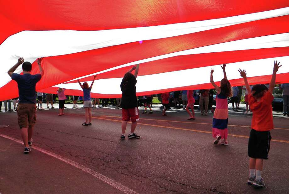 ADVANCE FOR USE SUNDAY, SEPT. 1, 2013 AND THEREAFTER - In this Oct. 9, 2011 photo, children help hold up a giant American flag as it passes down Main Street during the annual Labor Day parade in Newtown, Conn. The town's upcoming 2013 parade comes nearly nine months after shootings at Sandy Hook Elementary School left 26 dead, 20 of them children. In 2011, the event was postponed because of Tropical Storm Irene. Photo: Chris Sullivan