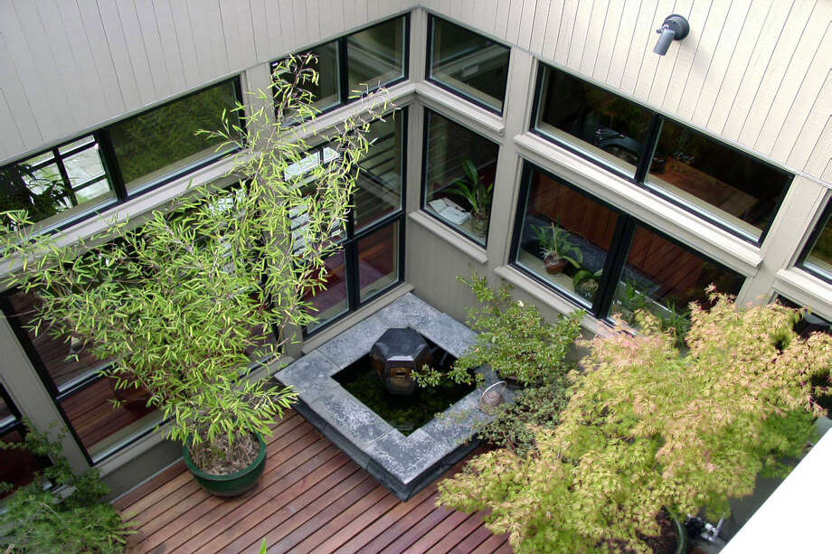 "The atrium ""was one example of the type of playfulness this residence offers the occupants. The 'exterior/interior' room provides a stage set where both natural and artificial light at night can playfully interact with activities associated with the other parts of the upper floor."" Photo: Castanes Architects"