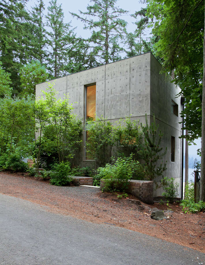 """From the outside, the home is an anonymous, almost austere, monumental concrete facade anchored deep into the hillside on a waterfront property,"" according to the writeup. ""Much of the home is hidden behind the two-story concrete face.""The 18-inch concrete exterior wall and exposed concrete inside ""reduce energy costs by serving as a thermal mass that naturally cools the home in the summer and holds warmth in the winter."" Photo: Andrew Waits, Roger Turk, Northlight Photography / © Andrew Waits"