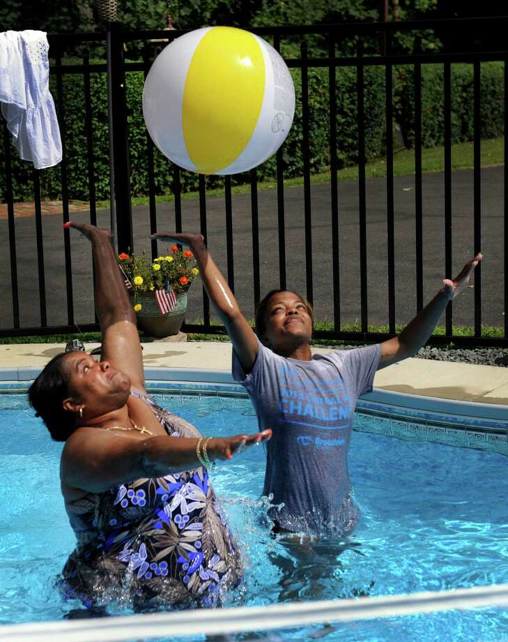Marcia Dyer, left, and Ashley Rogers, join in a game of volleyball at an end-of-summer pool party on Great Plain Road in Danbury, Conn. Wednesday, August 28, 2013. Photo: Carol Kaliff / The News-Times