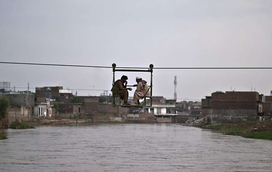 Bridge traffic: Two Pakistani men chat while crossing a stream on a self-propelled 