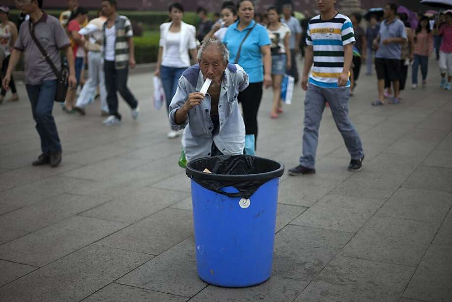 His quest for plastics will resume shortly: An elderly collector of recyclables takes a popsicle break while searching trash bins in 