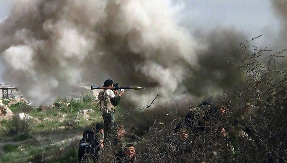 EDITOR'S NOTE: This slideshow contains graphic imagesAn image grab taken from a video shows opposition fighter holding a rocket propelled grenade (RPG) as his fellow comrades take cover from an attack by regime forces on August 26, 2013 during clashes over the strategic area of Khanasser, situated on the only road linking Aleppo to central Syria. Rebels had in recent days captured several villages in Aleppo province, much of which is already in the hands of anti-regime fighters, before taking Khanasser, situated on the highway to Hama in central Syria, thus cutting the army's only supply route to the northern province. Photo: AFP, AFP/Getty Images / 2013 AFP