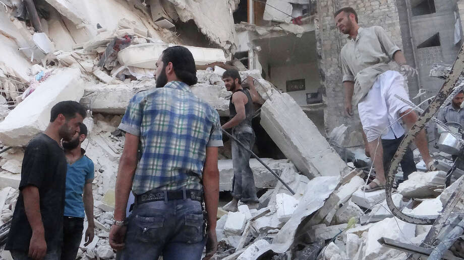 People search through the rubble of a building which collapsed after it was allegedly bombed from the air during clashes between rebel fighter and pro-government troops on August 16, 2013, in the northern Syrian city of Aleppo. Syria's government said it has nothing to hide from a UN team of chemical weapons inspectors that it expects to visit the war-ravaged country in the coming days. Photo: AFP, AFP/Getty Images / 2013 AFP