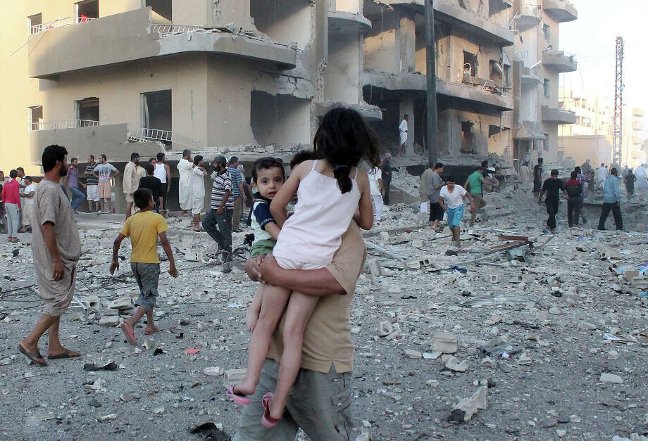 "A man carries two children away from the scene of an explosion in the northern Syrian city of Raqqa, early on August 7, 2013. UN weapons inspectors tasked with looking into claims of chemical weapons use in Syria are ""completing their preparations"" in The Hague before heading to Damascus, the United Nations said. Photo: AFP, AFP/Getty Images / 2013 AFP"