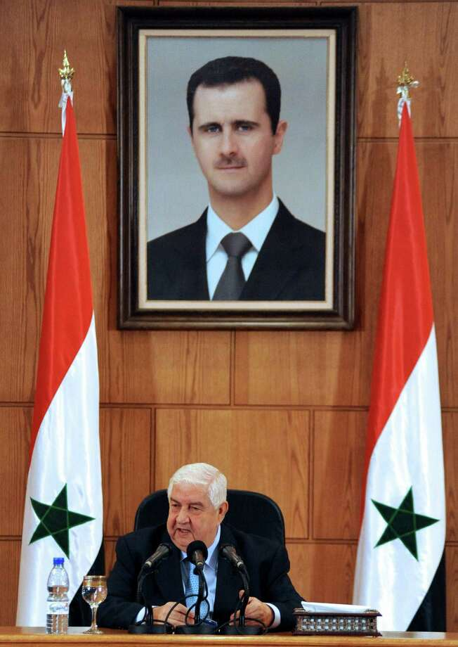 "Syrian Foreign Minister Walid Muallem, shown under a portrait of President Bashar Assad, said Tuesday in Damascus that the government has defenses that would ""surprise"" the world. Photo: AFP / Getty Images"