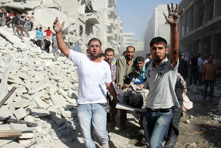 Syrian men evacuate a victim following an air strike by regime forces in the northern city of Aleppo on August 26, 2013. Syria's opposition accused pro-regime forces of opening fire at UN weapons inspectors on their way to a suspected chemical weapons site outside Damascus in a bid to hinder their investigation. Photo: AFP, AFP/Getty Images / 2013 AFP