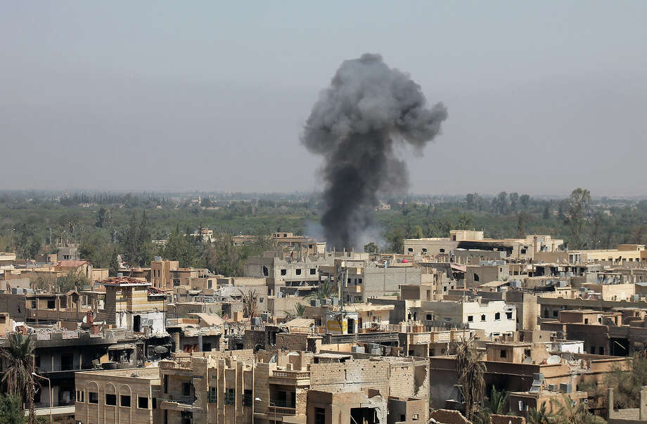 """Smoke rises from buildings in Syria's eastern town of Deir Ezzor on August 13, 2013 following an airstrike by government forces. Syrian opposition activists, including National Coalition members, have drawn up a transitional roadmap including a call for national reconciliation and justice for """"all of Syria's victims,"""" a statement said. Photo: AFP, AFP/Getty Images / 2013 AFP"""