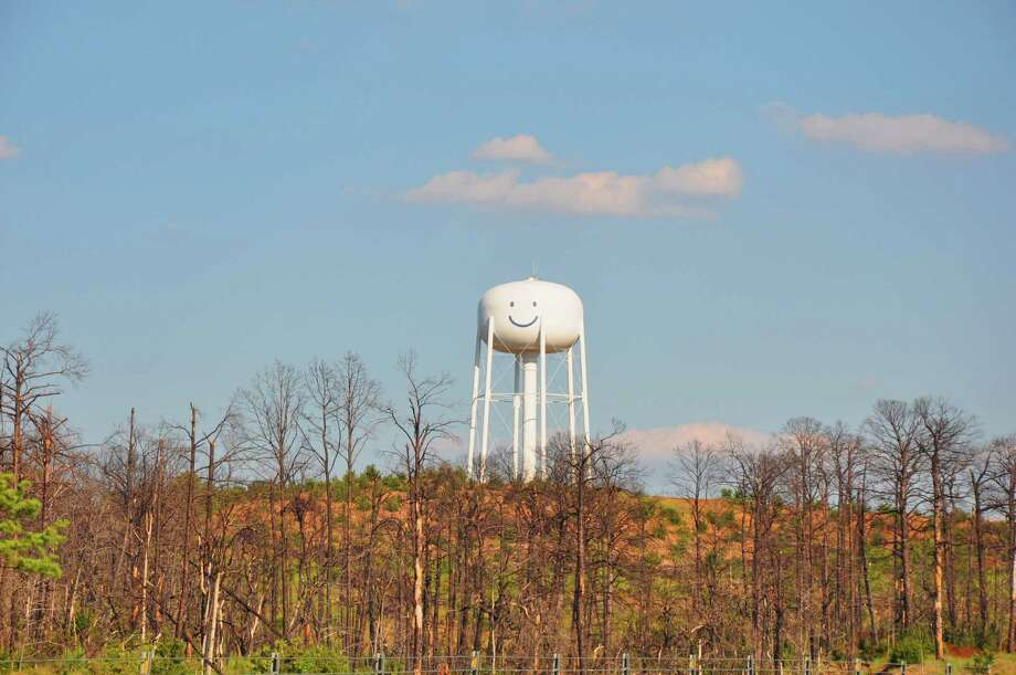 The smiley face water tower on Texas 71 in Bastrop looks out over the burned forest of Lost Pines. Photo: Dylan Aguilar