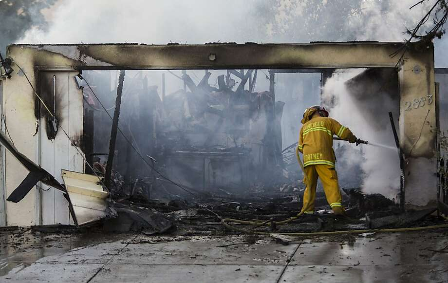 Firefighters battle the blaze that jumped a creek and set the roof of one Fairfield house afire, then spread. Five homes were destroyed, 10 others damaged. Photo: Ken James, Special To The Chronicle