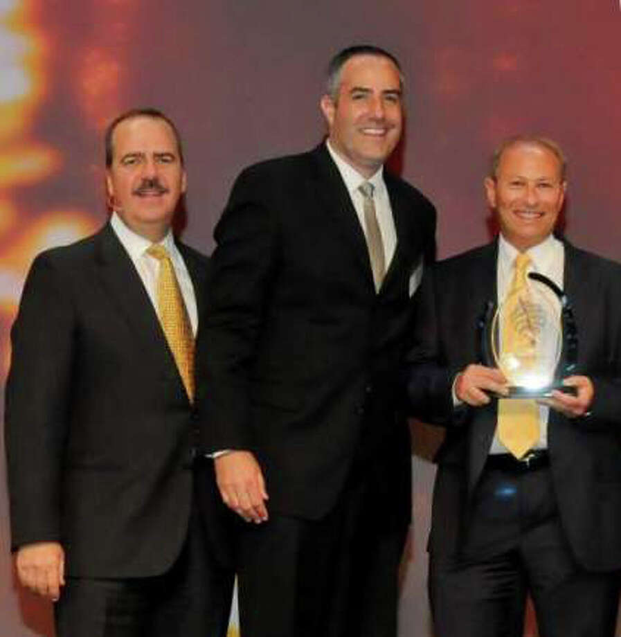 Steve Spivak, Tauck's director of national sales, and Rick Baron, managing director of worldwide accounts, accept an award from Virtuoso chairman and CEO Matthew Upchurch, in Las Vegas earlier this month. Photo: Contributed Photo