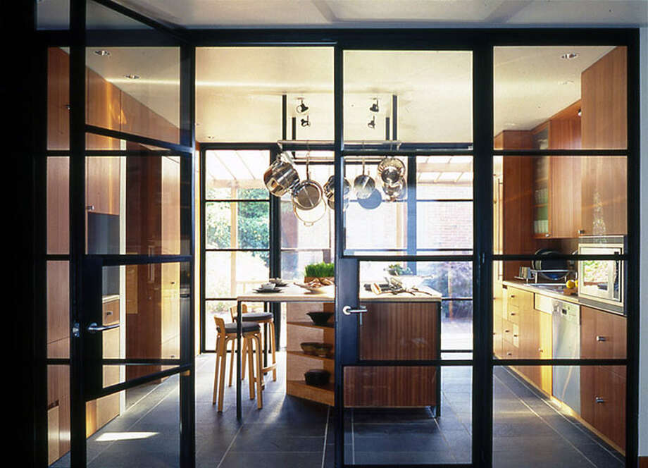 """Interior walls were removed and the floor plan opened to focus on the kitchen, the heart of this home, where glass and steel doors illuminate like lanterns when viewed from inside and out."" Photo: David Coleman"