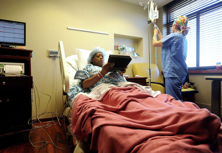 Moments before undergoing a Caesarean section at Baptist Hospital on Wednesday, Sparkle Simon holds a computer for family members during a Skype session with her husband Guy Simon. Guy Simon is currently stationed at an Army base in South Korea with plans to return home to meet his newborn daughter in about 12 days. Wendy Maedor is also pictured. 