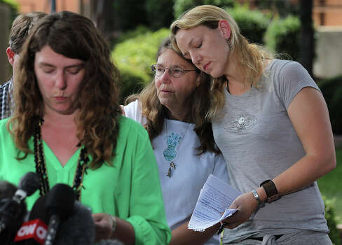 Kerry Cahill, right, hugs her mother, Joleen Cahill as her sister, Keely Vanacker addresses the media after Maj. Nidal Hasan is sentenced to death for capital murder at at trial in Fort Hood, Texas, Wednesday, Aug. 28, 2013.  Photo: Jerry Lara, San Antonio Express-News / ©2013 San Antonio Express-News