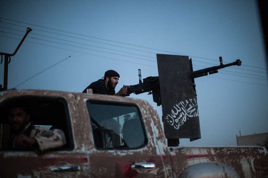 A member of the  Islamist Syrian opposition group Ahrar al-Sham fires against a position of the Committees for the Protection of the Kurdish People (YPG), a militia set up to protect Kurdish areas in Syria from opposing forces, during clashes in the countryside of the northern Syrian Raqqa province on August 25, 2013. Syrian Foreign Minister Walid Muallem said on August 27 the UN mission investigating alleged chemical weapons attacks in Damascus has been delayed until the following after rebels failed to guarantee the experts' safety. Photo: AFP, AFP/Getty Images / 2013 AFP