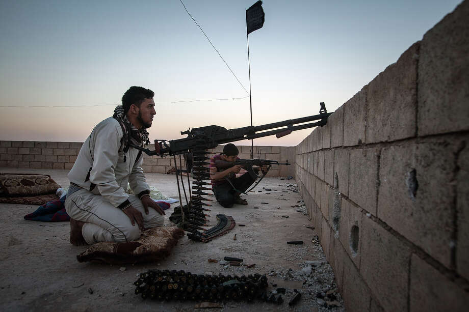 Members of the Islamic Kurdish Front aim their weapons at a position of fellow Kurdish fighters from the Committees for the Protection of the Kurdish People (YPG) during clashes with the militia, reportedly set up to protect the Kurdish areas in Syria from opposing forces, on the outskirts of the northern Syrian city of Raqqa, on August 23, 2013. More than 100,000 people have died in Syria's war, the UN says. Photo: AFP, AFP/Getty Images / 2013 AFP