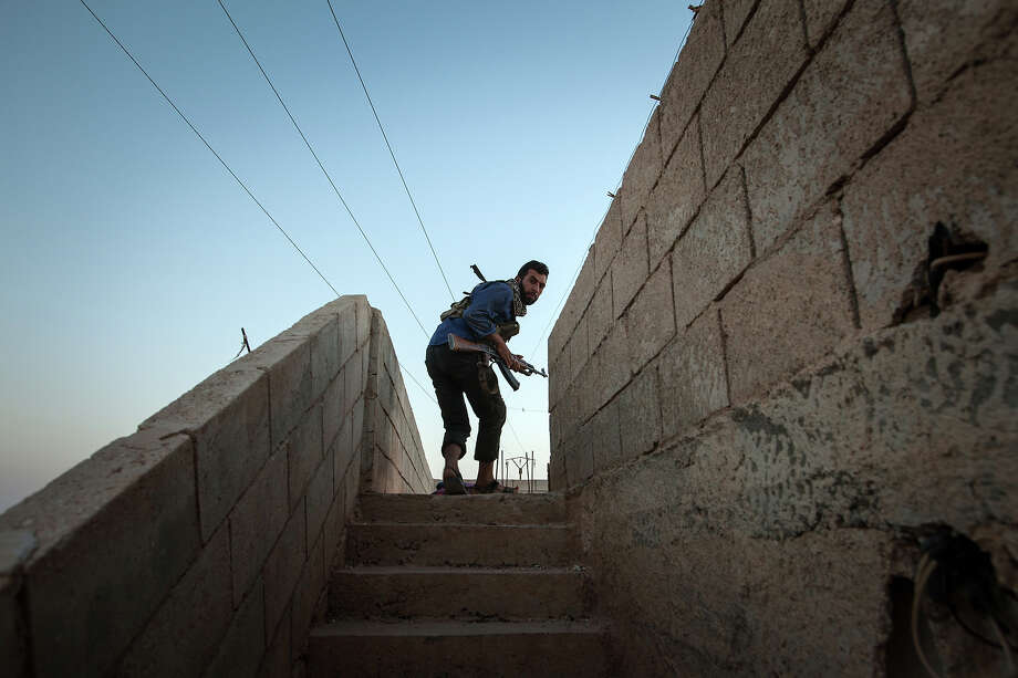A member of the Islamic Kurdish Front ducks to avoid sniper fire as he walks up stairs during clashes with fellow Kurdish fighters of from the Committees for the Protection of the Kurdish People (YPG), a militia set up to protect the Kurdish areas in Syria from opposing forces, on the outskirts of the northern Syrian city of Raqqa, on August 23, 2013. More than 100,000 people have died in Syria's war, the UN says. Photo: AFP, AFP/Getty Images / 2013 AFP